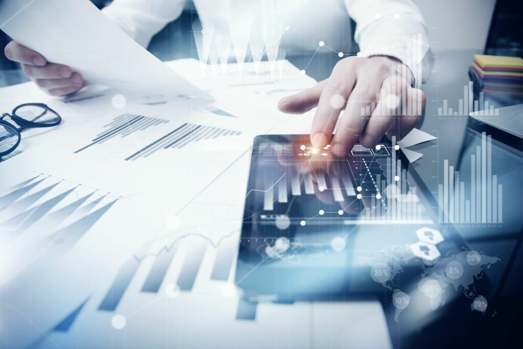accounting software on a tablet surrounded by financial sheets